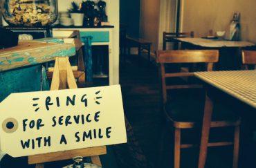 """Photo of a handwritten label in a cafe that says """"Ring for service with a smile"""""""