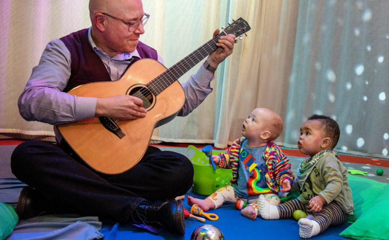 Babies listening to a man play the guitar as part of My First Protest Song