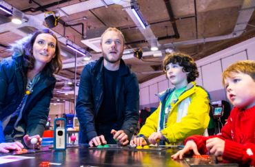 A family enjoying gaming together at the National Videogame Museum.